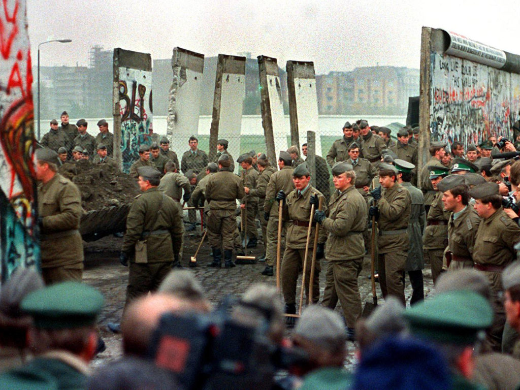 East and West German soldiers remove some of the first sections of the Berlin Wall